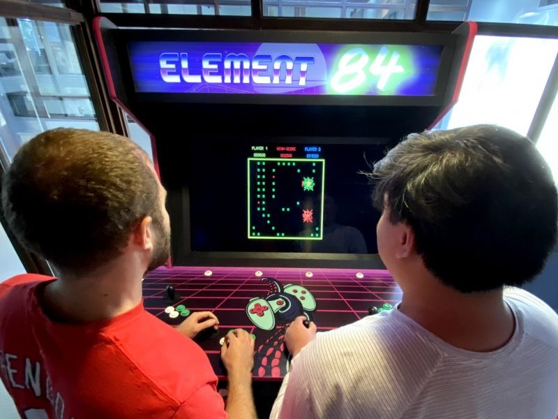 Two men playing games on the Element 84 arcade